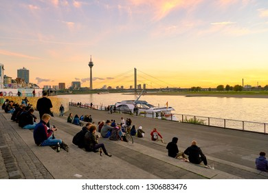 DUSSELDORF, GERMANY - CIRCA SEPTEMBER, 2018: people sitting on the steps down to the promenade by the Rhine River in Duesseldorf