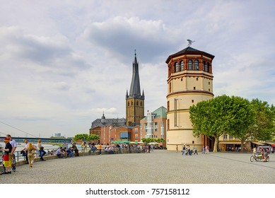 DUSSELDORF, GERMANY, JUN.13, 2010: View on city river walk with people, roman cathedral church and tower. People and tourists on open city square along riverwalk. Classical european architecture
