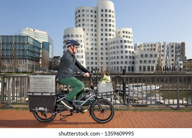 Dusseldorf / Germany – March 30, 2019: Urban cyclist with cargo bike in media harbor district on March 30, 2019 in Dusseldorf.