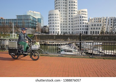 Dusseldorf / Germany – March 30, 2019: Cyclist with cargo ebike and delivery boxes cycling along modern media harbor district on March 30, 2019 in Dusseldorf.