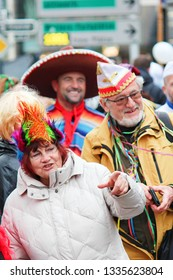 Dusseldorf, Germany - March 3rd 2019: Older couple of seniors in funny carnival hats following the festival crowd in the streets of German Dusseldorf. The woman is pointing with a finger.