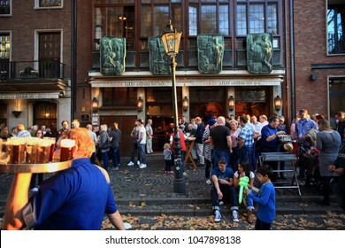 DUSSELDORF, GERMANY - OCTOBER 18, 2014: People and waiter holding an Altbier (Dusseldorf local beer) tablet in front of the Uerige pub in the old town on October 18, 2014 in Dusseldorf.