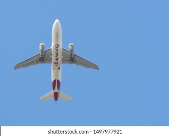 Dusseldorf / Germany - September 4, 2019: View from below of undercarriage of a Eurowings low cost carrier plane flying against a pale blue sky.Image left with copy space right - Image
