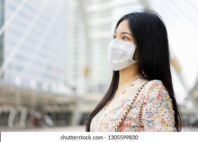 Dust contamination healthcare and air pollution concept, young Asian Chinese Thai woman wearing respiratory mask protect and filter pm2.5 (particulate matter) against traffic and dust in city