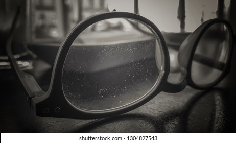 dust covered lens of reading glasses seen in black and white and back lit