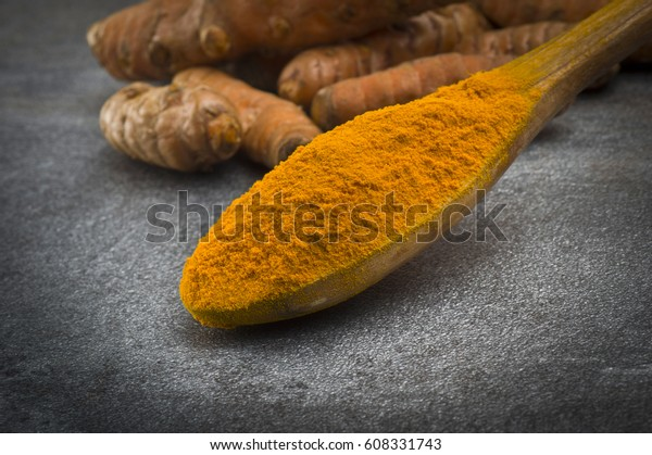 dust of ground turmeric on the grey background