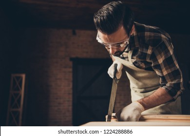 Dust sawdust chip hobby leisure handy man fix repair repairman concept. Low angle close up photo portrait of focused serious brunet handsome strong muscular casual guy using silver saw wooden blocks