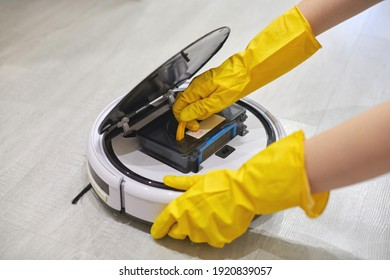Dust storage box case of robotic vacuum cleaner in gloved hands. Woman inserting filter and container to collect dust and debris. Vacuum cleaning concept, close up.
