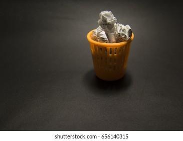The dustbin of forgotten ideas, wastepaper basket on black background