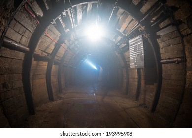 dusted tunnel in copper mine, silhouette of miner with flashlight