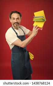 For dusting surfaces. Mature man holding cleaning cloths of assorted colors. Eldery housekeeper presenting cleaning towels. Senior man in apron with rubber gloves. Household worker. Household service.