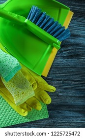 Dustpan broom sponges protective gloves washcloth on wooden board.