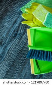 Dustpan broom sponges safety gloves washcloth on wooden board.