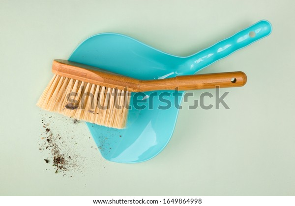 Dustpan and brush and a pile of dust and dirt, top view. House chores, cleaning conncept.