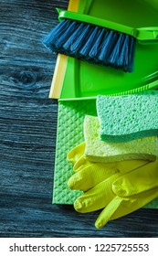Dustpan brush sponges protective gloves washcloth on wooden board.