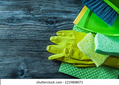 Dustpan brush sponges safety gloves washcloth on wooden board.