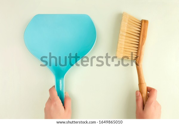 Dustpan and brush in woman hands. Cleaning concept.