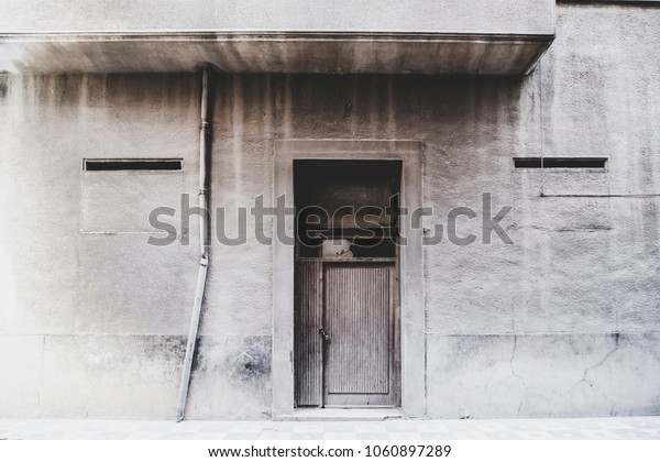 Dusty and aged concrete building facade, wooden door with broken glass