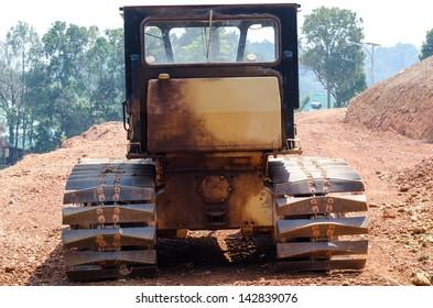 Dusty big bulldozer, isolated on pure