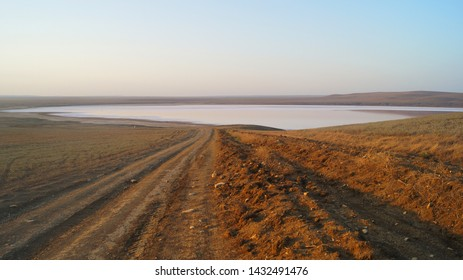 A dusty evening road from a hill to Koyazhskoe salt lake, lying among wastelands in Crimea.