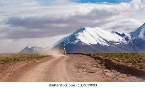 dusty gravel road in the Andes mountains Bolivia with an off-road car driving fast