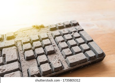 Dusty keyboard extreme on wood table. dusty computer keyboard. An abstract concept of an abandoned.