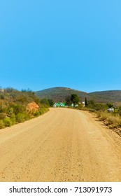 The dusty road to the town of Calitzdorp with blue skies.