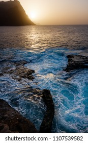 Dusty sunset and turbulent waves at the rocky beach of Santo Antao Island