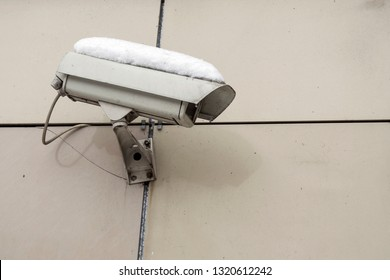 dusty surveillance camera covered with snow.