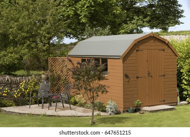 A Dutch barn style garden shed with a patio in a English country garden