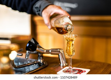 A Dutch bartender in Amsterdam pours jenever / genever into a tulip shot glass, as part of a tradition called kopstootje.