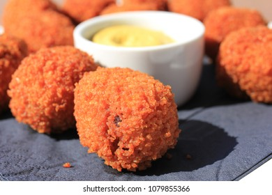 Dutch Bitterballen with mustard, warm stuffed fried meatballs, served in the Netherlands