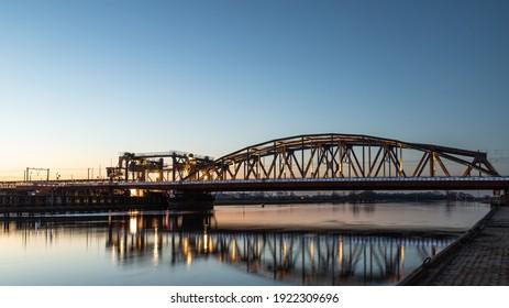 Dutch blue illuminated IJsselspoorbridge (Zutphen) over the high water of the river 'de ijssel'.