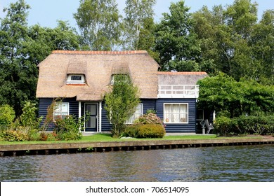 Dutch blue wooden house in traditional style, typical straw roof and charming garden terrace along water in Giethoorn, 'little Venice', Netherlands