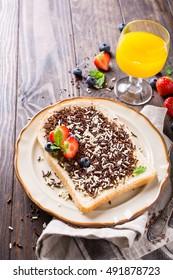 Dutch breakfast, slice of bread with hagelslag chocolate sprinkles and berries. Copy space.