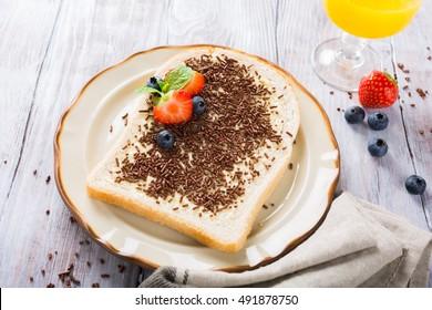 Dutch breakfast, slice of bread with hagelslag chocolate sprinkles and berries.