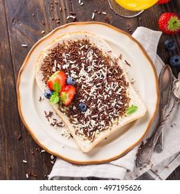 Dutch breakfast, slice of bread with hagelslag chocolate sprinkles and berries. Top view.