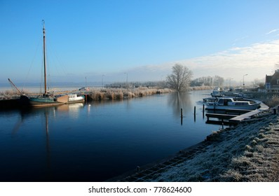 Dutch canal in the winter, frozen water and some boats in the harbour