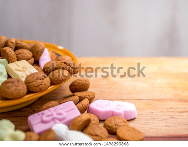 Dutch candy called Pepernoten and Schuimpjes for the Dutch holiday called Sinterklaas on december 5th, in a bowl on a red wooden table. Blurred background with room for text.