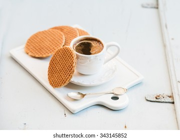 Dutch caramel stroopwafels and cup of black coffee on white ceramic serving board over light blue wooden backdrop, selective focus