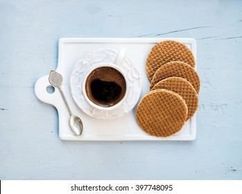 Dutch caramel stroopwafels and cup of black coffee on white ceramic serving board over light blue wooden backdrop, top view, horizontal