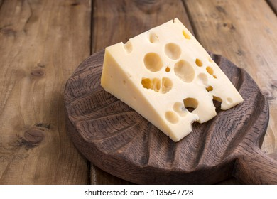 Dutch cheese with holes on a wooden old board. Vintage photo. Dairy. Free space for text. Copy space.