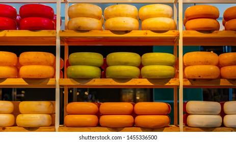 Dutch cheeses, edam, gouda, whole round wheels on wooden shelf, cheese store in Rotterdam, Netherlands. Texture, background