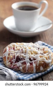 Dutch cinnamon bun glazed with icing and cup of black coffee