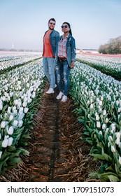 Dutch colourful tulip fields, couple in flower field , dutch tulips, men and woman in white tulip field in the Netherlands near Noordoostpolder Holland