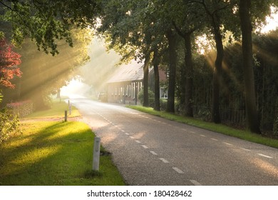 Dutch country road and farm in early morning sun after the rain