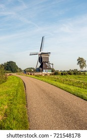 Dutch country road with a wooden hollow post polder mill from 1762, restored in 1953. The mill is now a national monument and no longer in use as a polder mill.