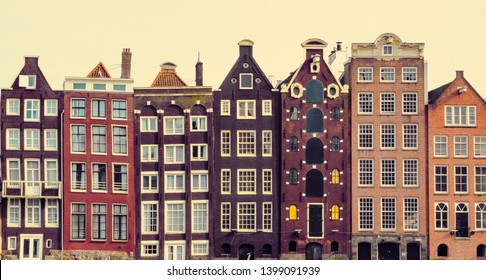 Dutch dancing houses on on Damrak canal, embankment of the Amstel River. Colorful chocolate houses in the old side of Amsterdam, Netherlands.
