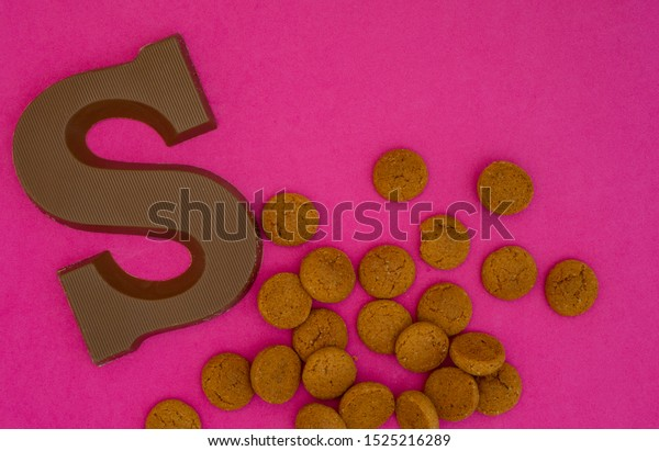 Dutch fest called Sinterklaas composition. With a chocolate letter S and candy called pepernoten. Top view on a purple background with room for text.