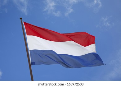 dutch flag blowing in the wind against a blue sky